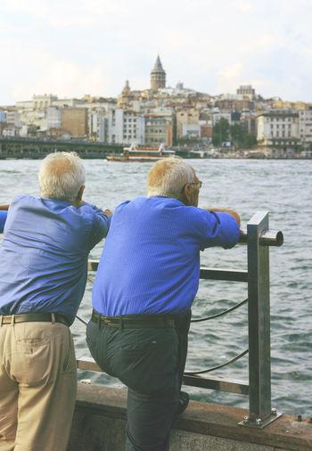 Men overlooking river against built structures