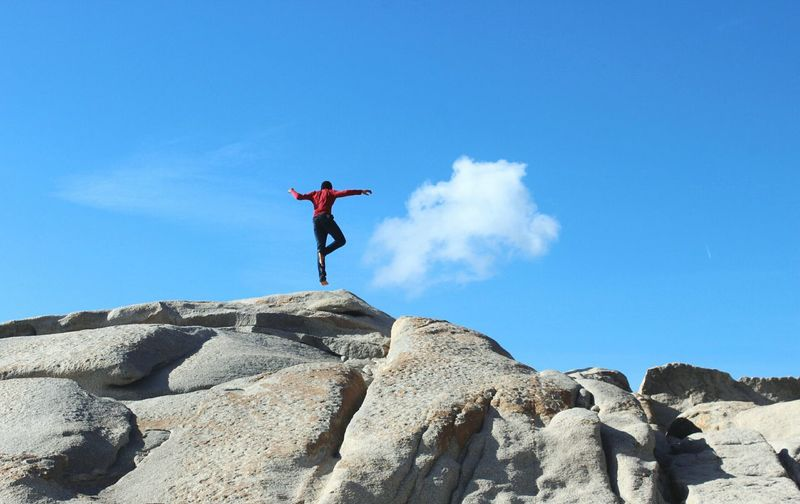 Low Angle View Of Person Levitating Over Rock Formation Against Blue Sky