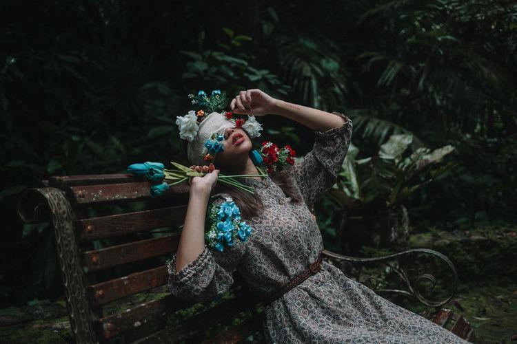 Full length of woman sitting against plants