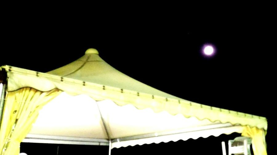 Low angle view of illuminated stage against clear sky at night