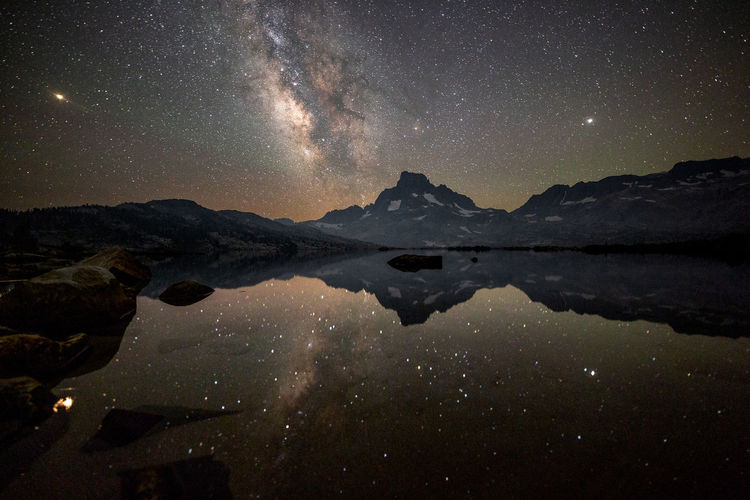 In our lifetime | JMT DAY 3 - MILKY WAY OVER BANNER PEAK AND THOUSAND ISLAND LAKE Milky Way over Banner Peak and Thousand Island Lake: JMT201803003 As the evening grew darker, the faint Milky Way appeared in the middle of the sky, contrary to the same galaxy appearing over the ridge line in mid-June. The wind stopped blowing, which promised a tranquil night with the stillness of Banner Peak in the water. Jupiter and Mars were traversing along with our galaxy across the sky strewn with thousands of stars, and I was simply mesmerized yet again. I recently finished reading a book called Black Hole Blues, chronicling the journey of scientists for over 50 years trying to detect gravitational waves, like Einstein had predicted. This effort, resulting in detecting its first gravitational wave in late 2015, having travelled the universe 1.4 billion light years, got me more curious about spacetime. Eventually (after billions of years, when the human species will be likely long gone) all the stars will die, like our sun will in about 5 billion years (although our galaxy will likely collide with the Andromeda Galaxy first). And they will turn into black holes, which eventually will also disappear. Regardless of any of that, it is truly remarkable to witness what already had happened billion light years ago in our lifetime. Thousand Island Lake, Inyo National Forest, CA Banner Peak Jupiter Mars Reflection Thousand Island Lake Astronomy Beauty In Nature Eastern Sierras Galaxy Lake Milky Way Mountain Nature Night No People Outdoors Reflection Scenics - Nature Sierra Nevada Sky Star - Space Stars Tranquil Scene Tranquility Water