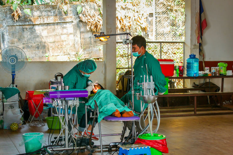 Chiang Rai, Thailand Help Thailand Hospital Dental Health Public Healthcare And Medicine Medical Volunteer Two People Adult Indoors  Sitting Full Length Men People Side View Togetherness Young Adult Real People Standing Day Table Males  Occupation Domestic Room Women Care Scrubs