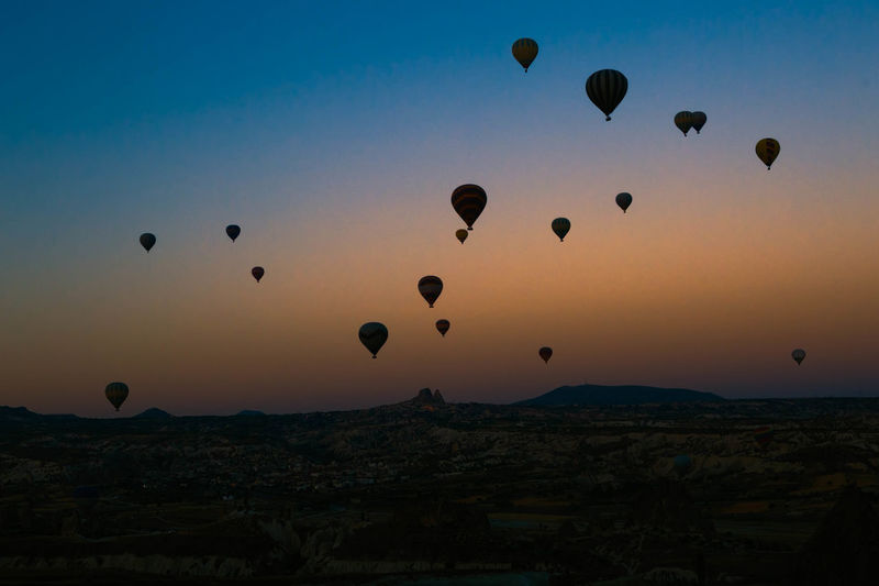 Hot air balloons flying over cappadocia during sunset