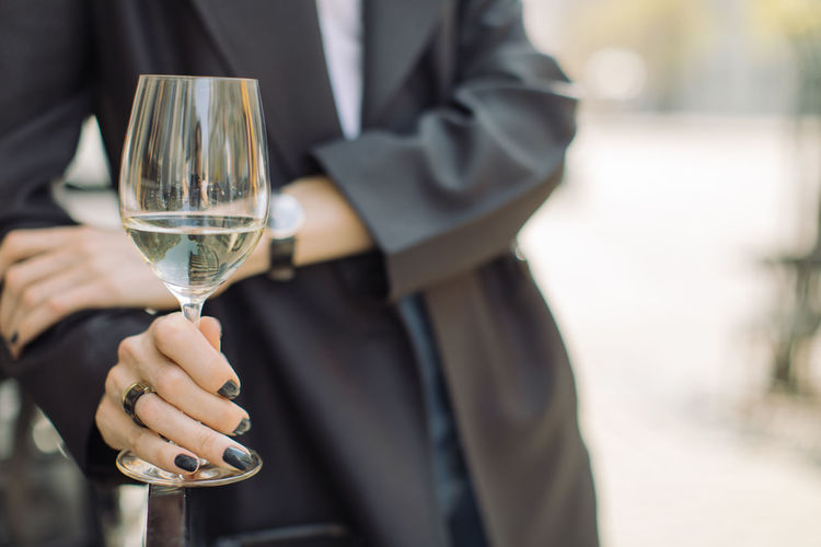 Holding One Person Focus On Foreground Well-dressed Midsection Wine Glass Suit Food And Drink Drink Front View Adult Refreshment Alcohol Day Standing Hand Champagne Flute Outdoors Fashion Fashionable Black Jacket Space For Text Accessories