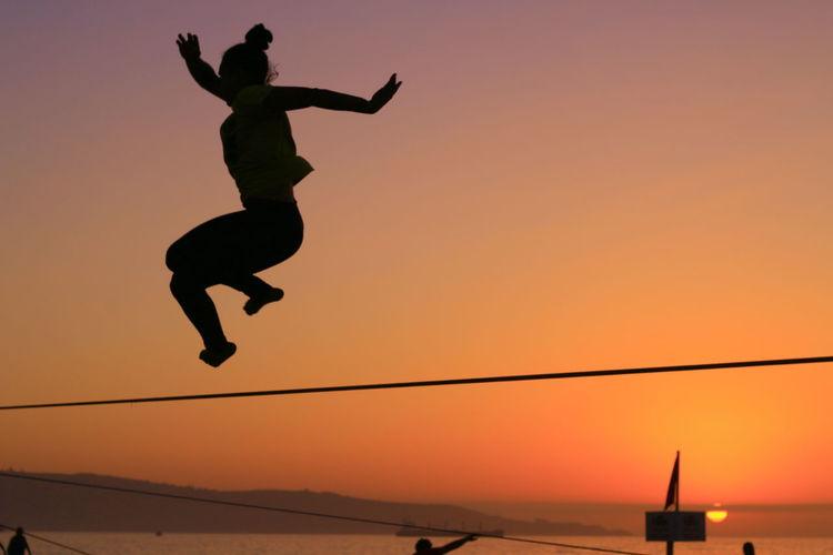 Womenaroundtheworld Jumping Tricks Sunset Sunsetsillhouette Mid-air Vitality Outdoors Girl Beach Sun Sky Sea And Sky Slackline Slacker Athlete