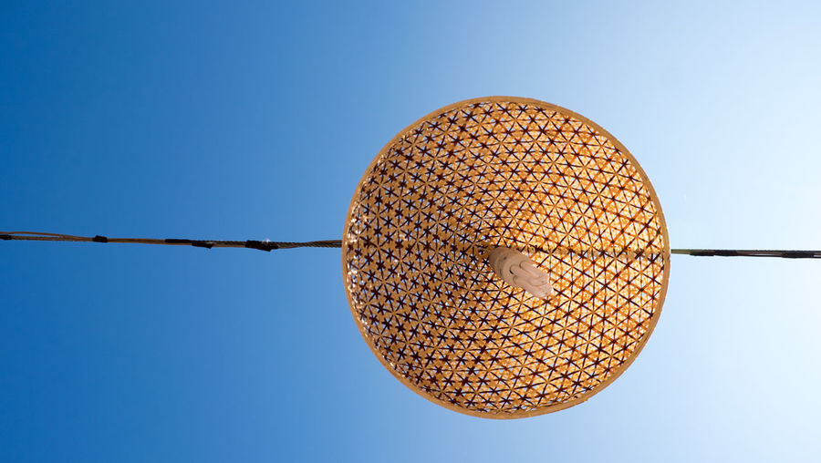 Low angle view of lighting equipment hanging against clear blue sky