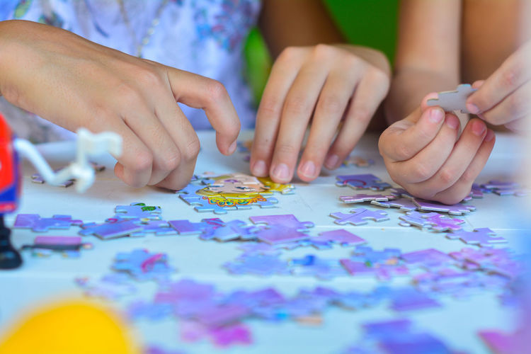 Cropped Image Of Children Playing Puzzle