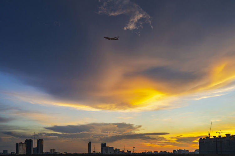 Low angle view of airplane flying over buildings against sky during sunset