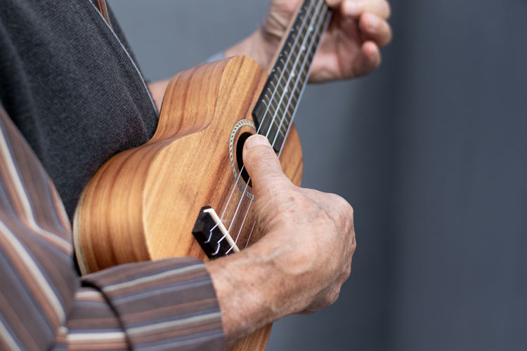 Midsection of man holding guitar