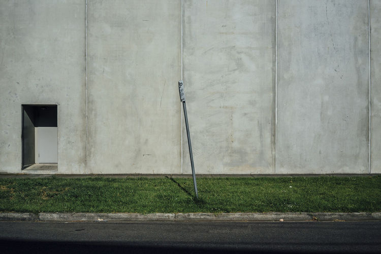 Gardening equipment on grassy field against wall