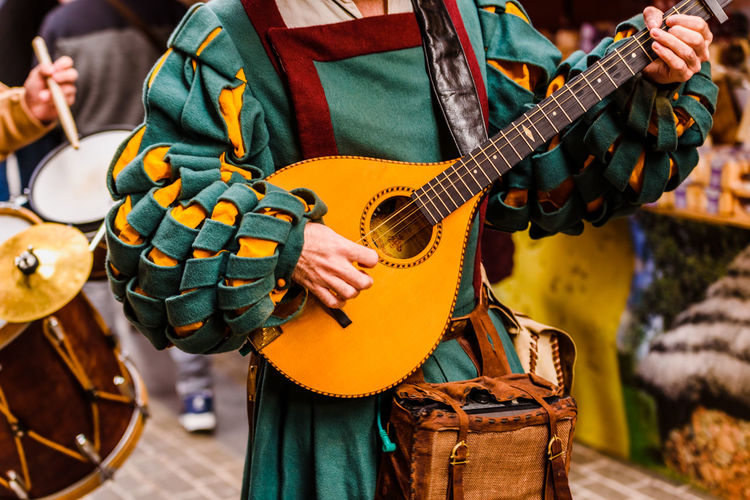 Midsection of man wearing traditional clothing while playing string instrument on road during parade