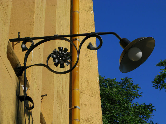 Low angle view of lamp mounted on wall against clear blue sky