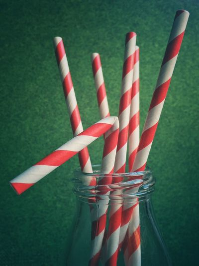 Close-up of red and white striped straws in glass bottle