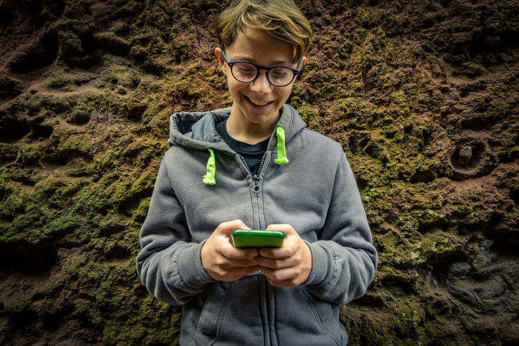 Close-up of smiling boy using smart phone standing by rock