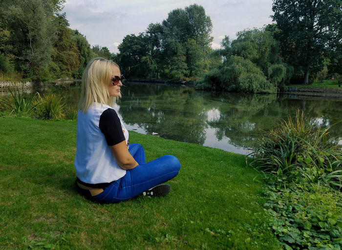 Side view of woman sitting on grass by lake