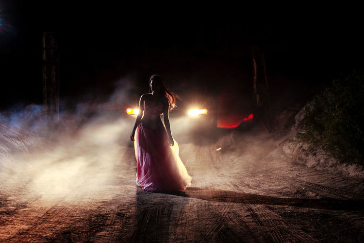 Full length of woman standing against car on dirt road at night
