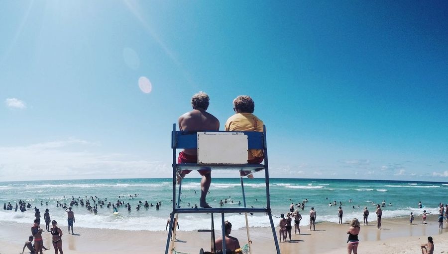 Rear view of man and woman sitting on lifeguard chair at beach against sky
