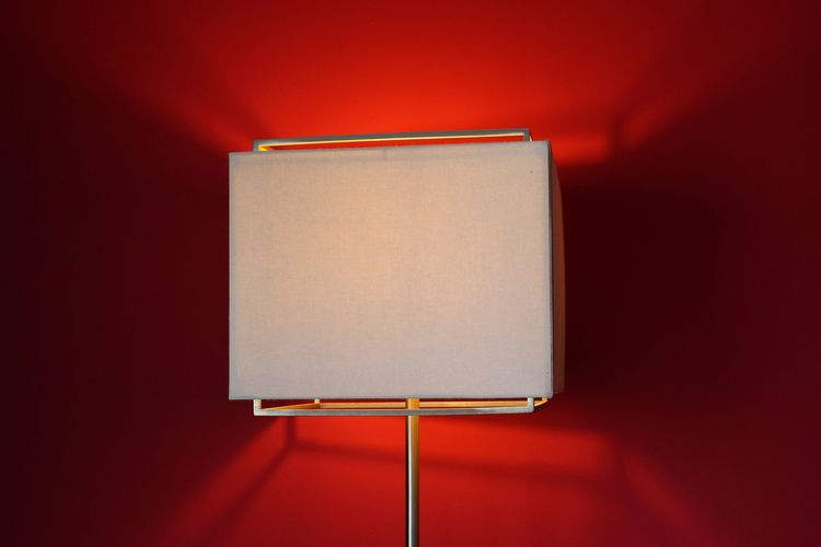 Close-up of illuminated modern lamp against red background