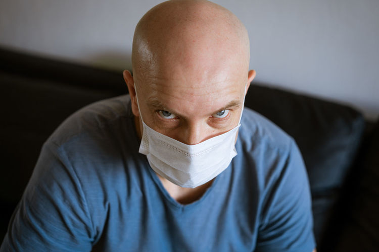 Portrait of a bald man wearing a protective mask