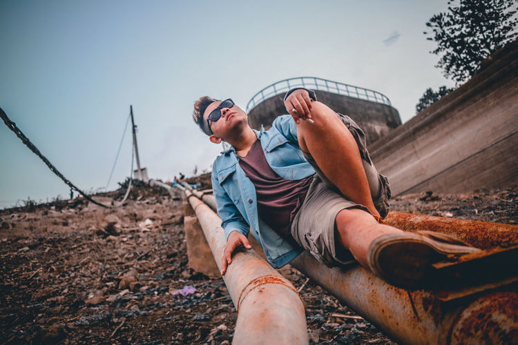 Man sitting on rusty pipe