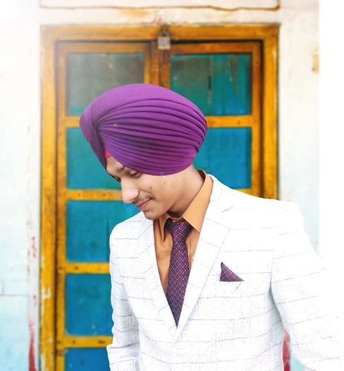 Smiling man in turban and suit standing against door
