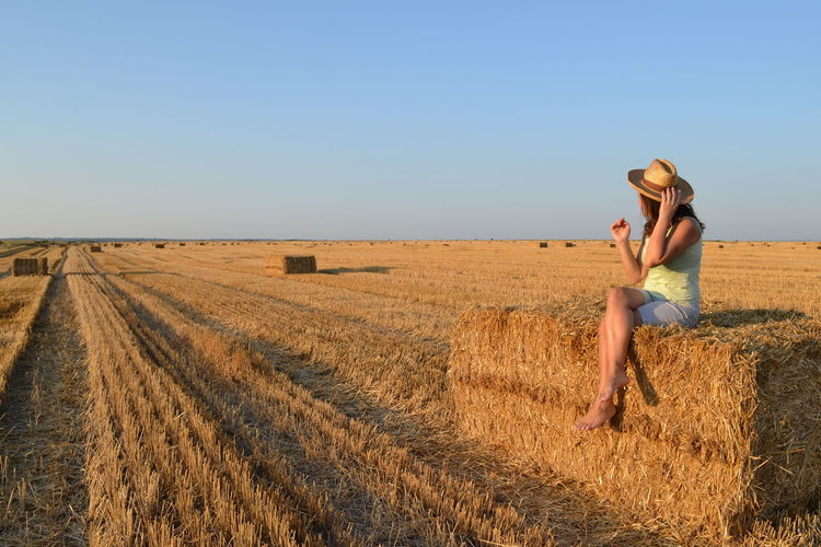 Full length of woman in hat sitting with legs crossed on hay bale against clear sky