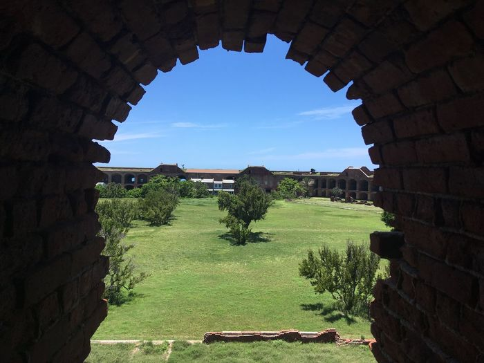 Exploring the fort Fort Jefferson Dry Tortugas Brick Structure Red Brick Greenery Courtyard View Blue Sky Arch Architecture Brick Fort Bricks Fort Architecture Built Structure Nature Sky No People Grass Field Beauty In Nature Blue Outdoors