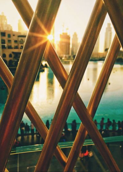 Close-up of railing against buildings at sunset