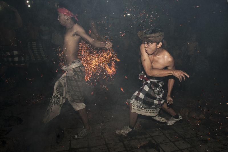 Shirtless Men Performing Stunt With Fire At Night