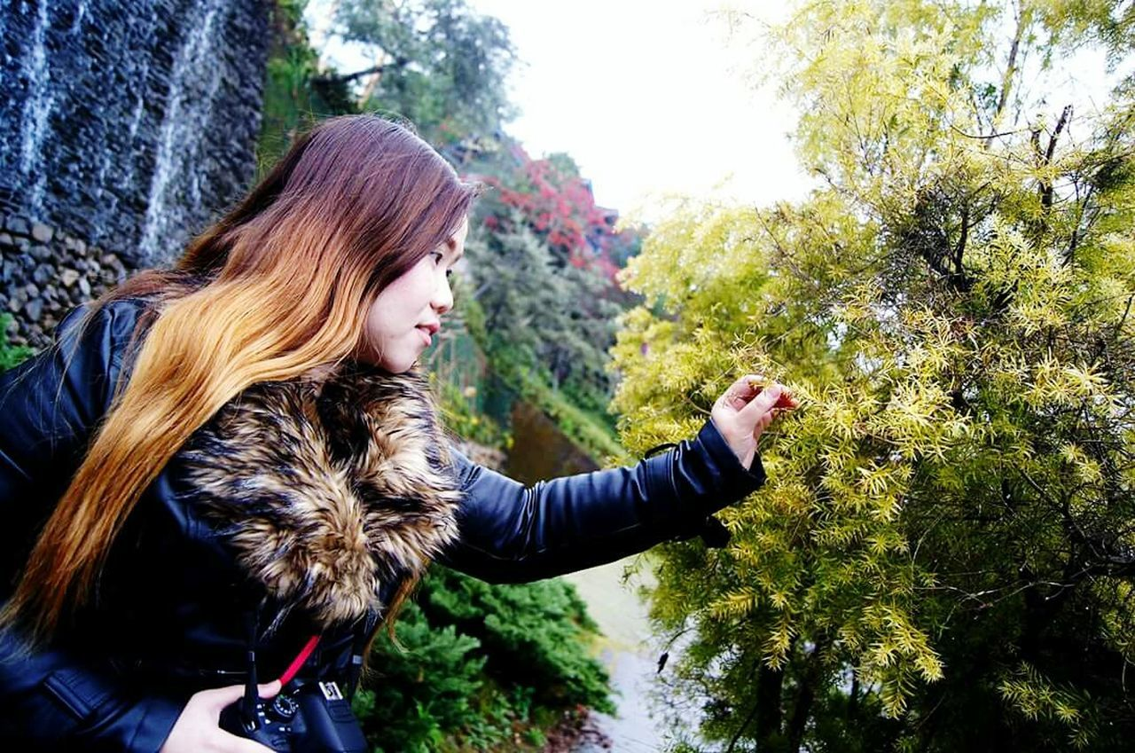 tree, real people, one person, young women, nature, young adult, outdoors, long hair, leisure activity, lifestyles, side view, day, warm clothing, beauty in nature, standing, beautiful woman, women, cold temperature, close-up, adult, people
