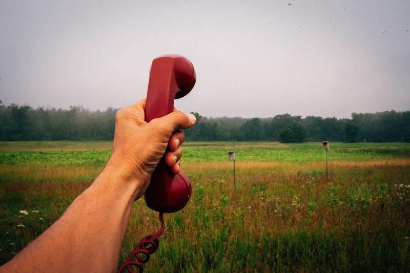 Cropped image of hand holding telephone receiver against grassy field