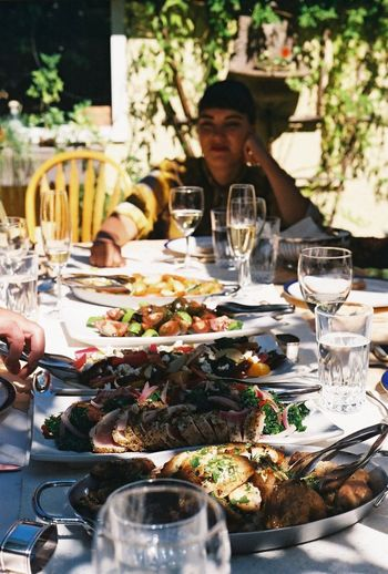 Woman sitting at table of food outdoors