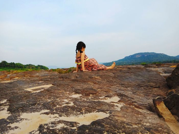 Rear view of girl sitting on rock against sky