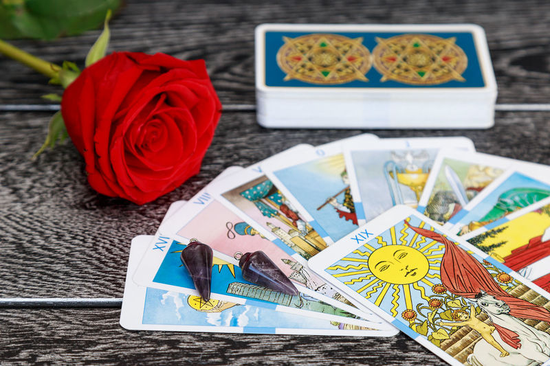 High Angle View Of Tarot Cards With Rose On Table