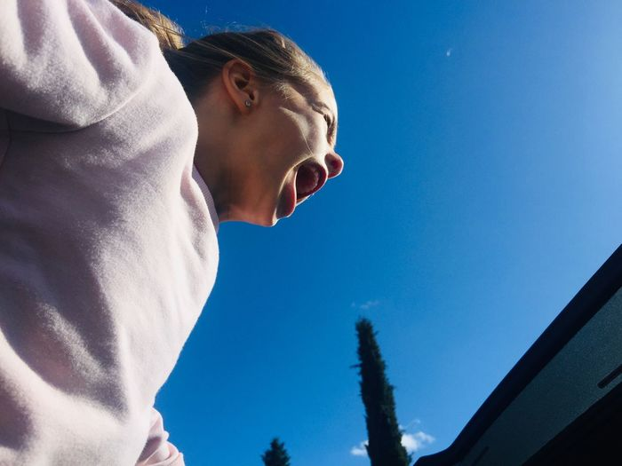 Low angle view of screaming girl against sky in summer