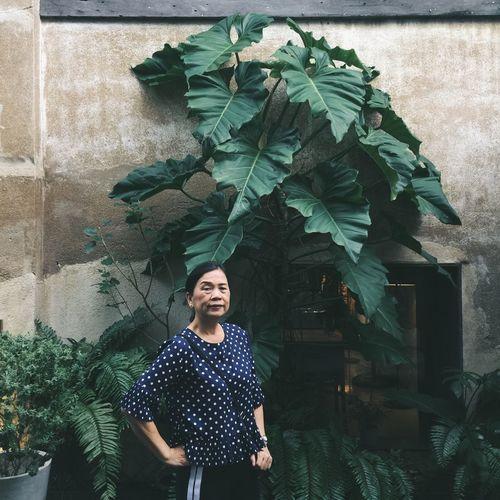 Portrait of senior woman standing against plants