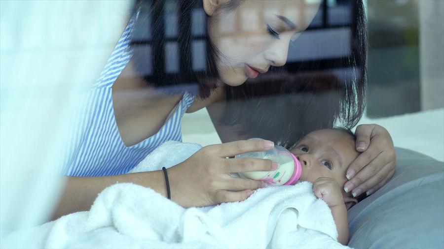 Mother feeding milk to cute baby son seen through glass window