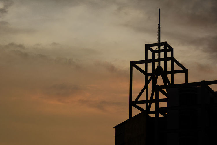 Low angle view of silhouette water tower against sky at sunset
