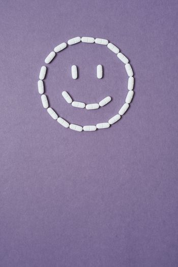 Directly above shot of medicines in smiley face shape on purple background
