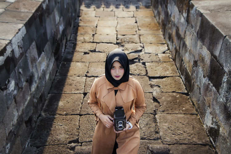 Muslim tourist woman wearing hijab / headscarf and brown coat at ratu boko temple, yogyakarta