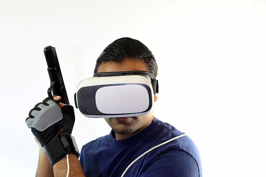 Young man with virtual reality headset holding gun up and to the side Console Display Futuristic Gamer Gaming Glasses Gloves Goggles Gun Headset Innovation New Pistol Playing Riffle Role Playing Game Shooter Shooting Technology Virtual Virtual Reality War Weapon White Background Wireless Technology