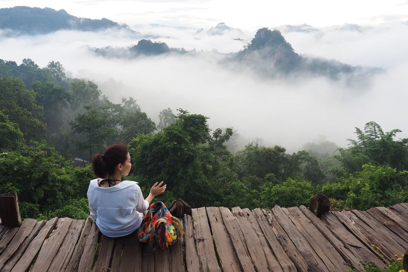 Rear view of woman sitting on wooden walkway over trees against sky