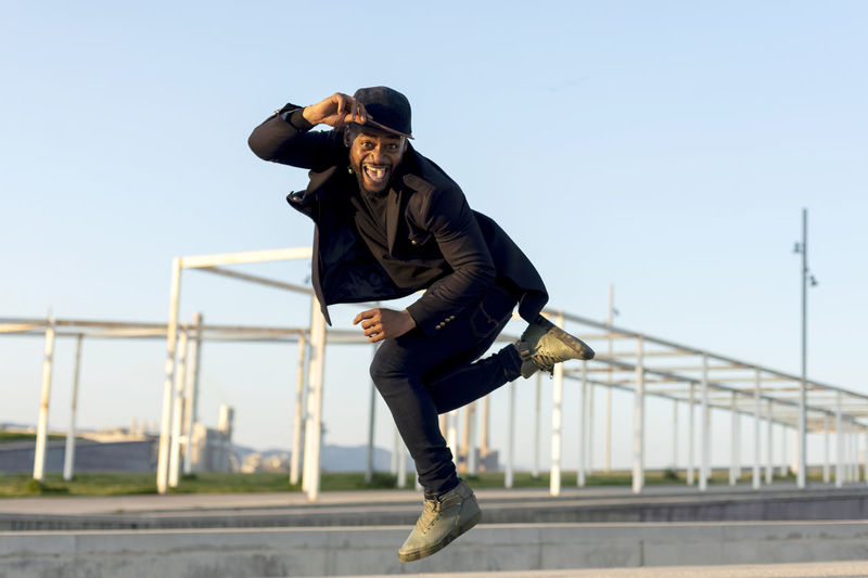 Stylish young male dancer in fashionable black clothes dancing blake dance on a street in the city on an autumn afternoon. Lifestyle. Full Length Real People One Person Lifestyles Hat Clothing Architecture Young Men Sky Railing Young Adult Leisure Activity Day Built Structure Men Nature Focus On Foreground Connection Jacket Outdoors African American Black Man