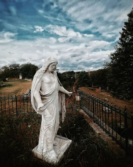 Statue of angel at cemetery against sky