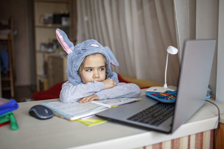 Cute girl learning over laptop on table at home