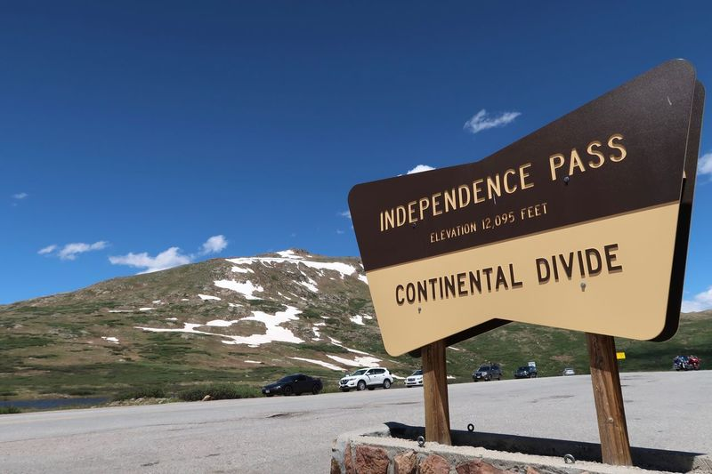 Landscape of mountain top and sign for Independence Pass in Colorado Snowcapped Mountain Continental Divide Landscape Colorado Independence Pass Text Communication Sign Western Script Sky Information Mountain Road Symbol Information Sign Nature Road Sign Blue No People Day