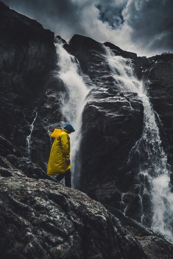 Side view of man by waterfall