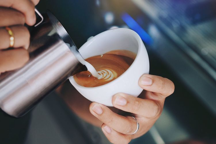 Cropped Hand Of Woman Pouring Milk In Cappuccino
