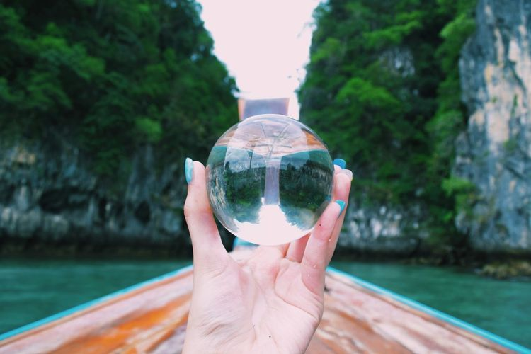 Cropped Hand Holding Crystal Ball With Reflection On Rocks On Boat
