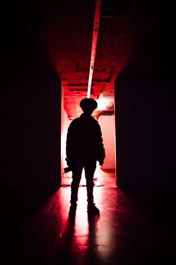 Rear view of silhouette man walking in corridor